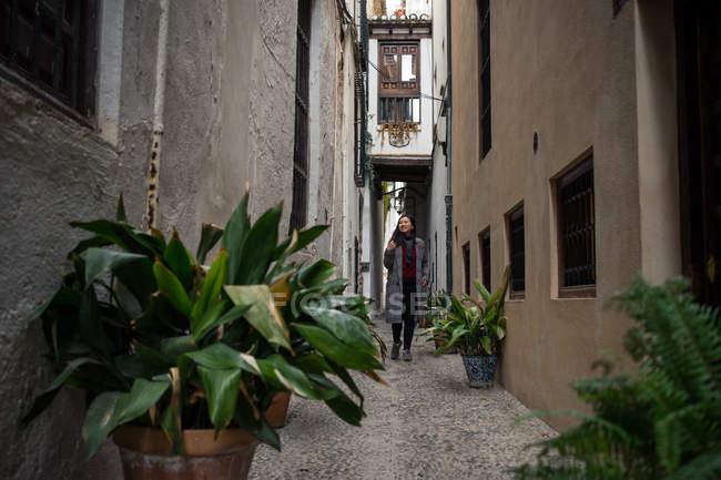 Excitado turista de ropa ocasional caminando por una estrecha callejuela con macetas de plantas verdes y edificios antiguos. - foto de stock