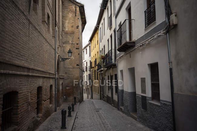 Antico vicolo di ciottoli con sentiero in pietra tra vecchi edifici in mattoni ad Albaicin a Granada in Spagna — Foto stock