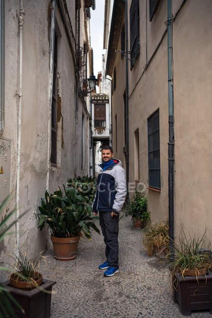Jóvenes de vacaciones con ropa caliente ocasional en la calle estrecha y vieja con macetas de plantas verdes. - foto de stock