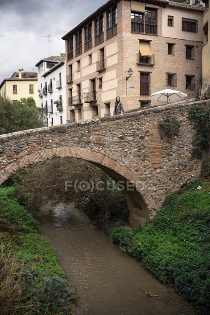 Viajeros en el antiguo puente cocido bajo el pequeño río entre plantas verdes con edificios en Albaicin en Granada, España. - foto de stock