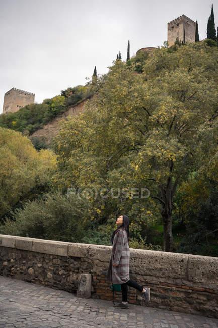 Vista lateral de las mujeres que viajan con abrigo ocasional sobre un antiguo puente adoquinado con vallas y verdes colinas con antiguo castillo. - foto de stock