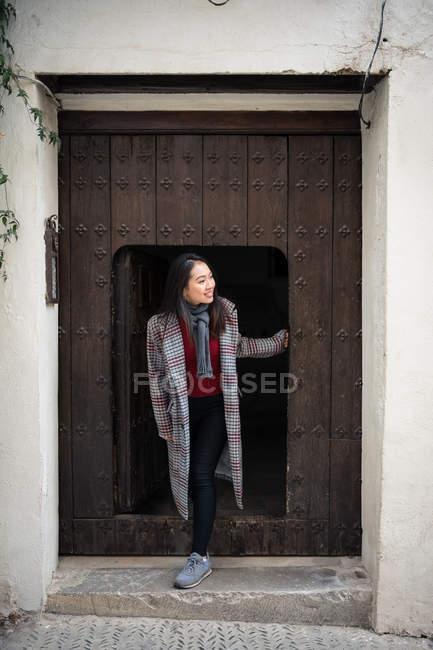 Взволнованная азиатская женщина в случайном пальто улыбается, выходя из маленькой двери и старого здания и отводя взгляд — стоковое фото