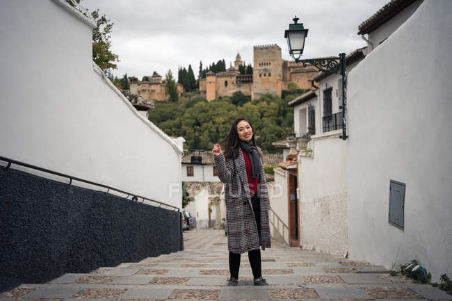Charming Asian female in casual coat standing on rocked stairs and looking in camera among buildings with powerful castle. - foto de stock