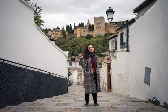 Affascinante asiatico femmina in casuale cappotto in piedi su scale a dondolo e guardando in macchina fotografica tra gli edifici con potente castello — Foto stock