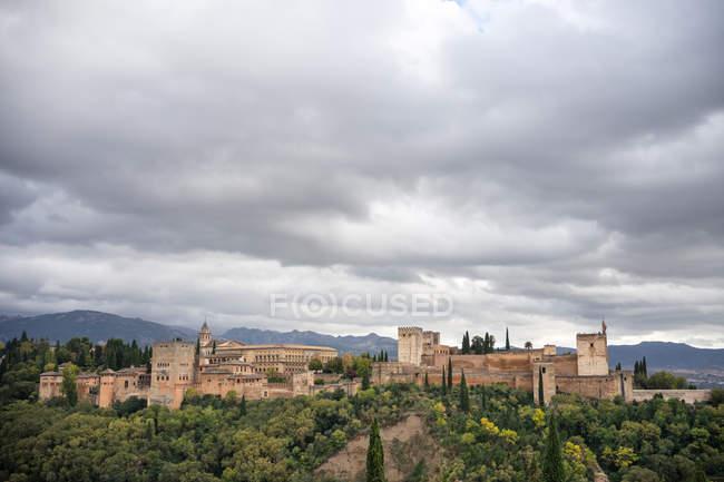 Castillo de la Alhambra de Alcazaba, antiguo y poderoso, en un gran terreno arbolado de árboles verdes cerca del casco antiguo, con montañas y cielo nublado en Granada. - foto de stock