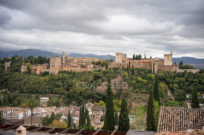 Потужний древній замок Алькасаба на великих зелених деревах біля старого міста з горами і хмарним небом у Гранаді. — стокове фото