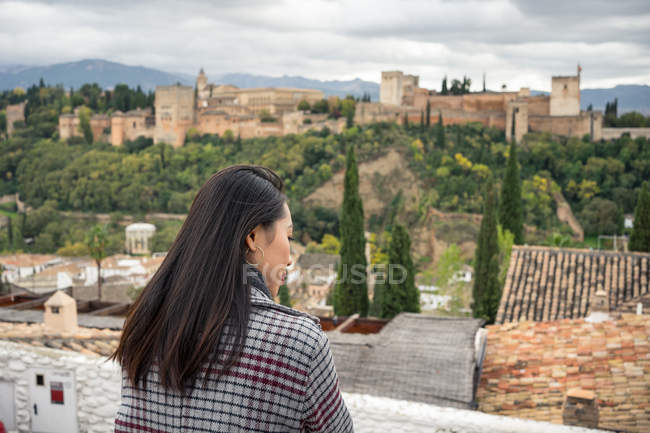 Back view of black-haired female in casual warm clothing delighting in view of old castle Alcazaba of Alhambra in Granada, Spain — Stock Photo