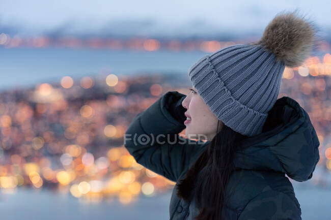 Excited young female in khaki down jacket and gray warm hat looking away and contemplating amazing winter view of city located on coast in evening — Stock Photo