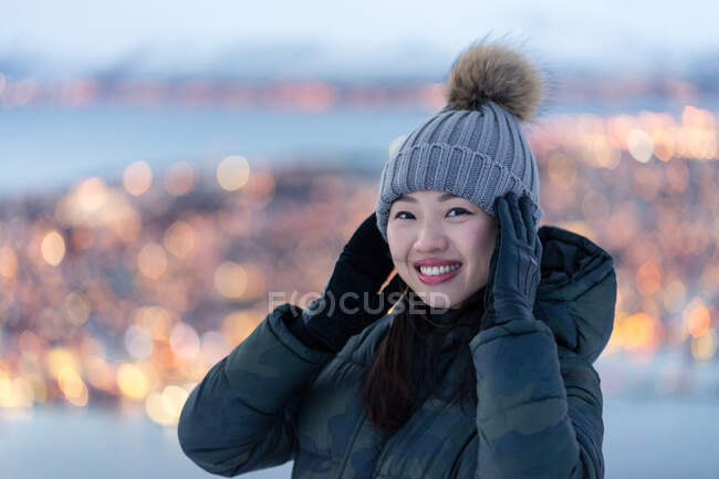Jeune femme excitée en duvet kaki et chapeau chaud gris regardant la caméra et contemplant une vue hivernale incroyable de la ville située sur la côte en soirée — Photo de stock