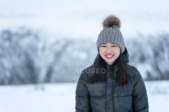 Magnífica fêmea feliz com olhos incríveis no escuro manchado jaqueta e chapéu quente cinza olhando para a câmera e sorrindo contra cenário turvo de parque nevado durante o dia — Fotografia de Stock