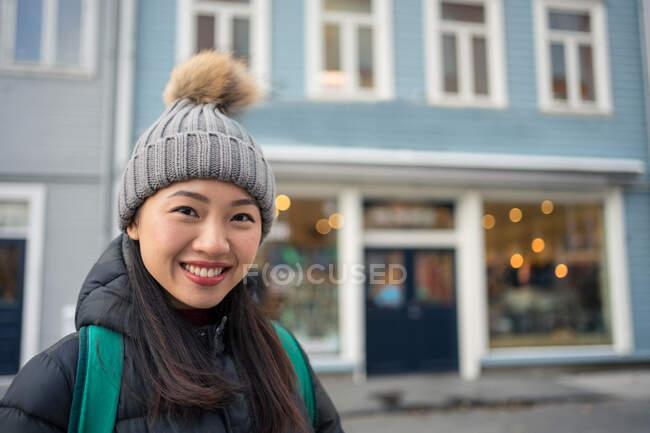 Linda mulher asiática adulta em roupas quentes olhando para a câmera e sorrindo contra o exterior turvo do edifício moderno azul no centro da cidade — Fotografia de Stock