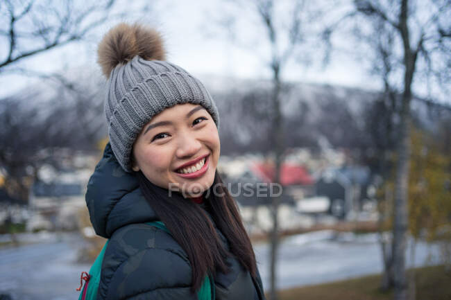 Attractive adult Asian woman in warm clothes with backpack smiling at camera while standing on street against blurred exterior of amazing triangle shaped church and snowy hills in Norway — Stock Photo