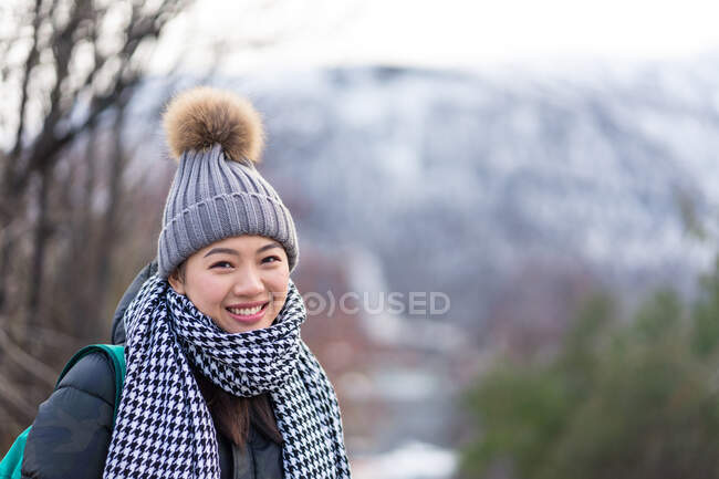 Asian female tourist in warm clothing at snowy nature — Stock Photo