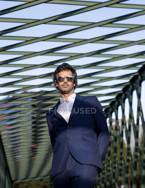 Content stylish businessman in elegant costume and sunglasses looking away in sunlight under metal construction — Stockfoto