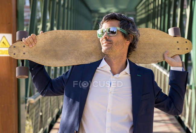 Content pleased businessman in suit and sunglasses raising wooden longboard and looking away in sunny daytime — Stock Photo
