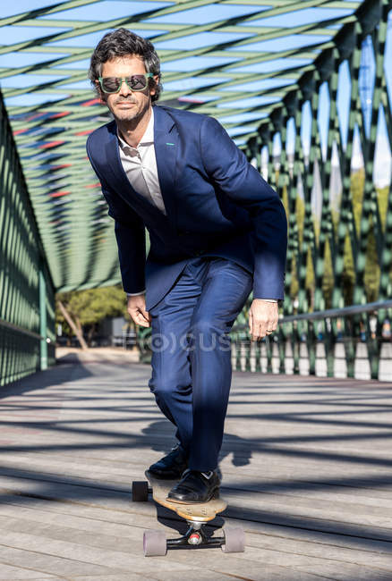 Content stylish businessman in trendy suit riding longboard along road with metal fence — Stock Photo