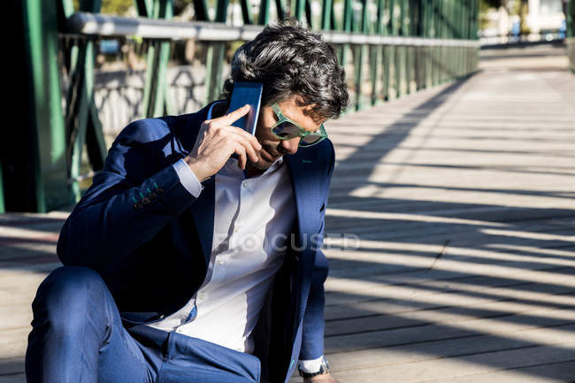 Pensive attentive businessman in elegant suit and sunglasses talking on mobile phone comfortably sitting on ground — Stock Photo