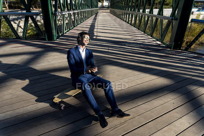 From above stylish businessman comfortably sitting on longboard and laughing on bridge — Stock Photo