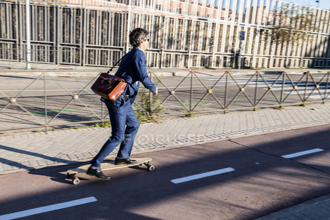 Content stylish businessman in classy suit on longboard driving down paved roadway in bright daytime — Photo de stock