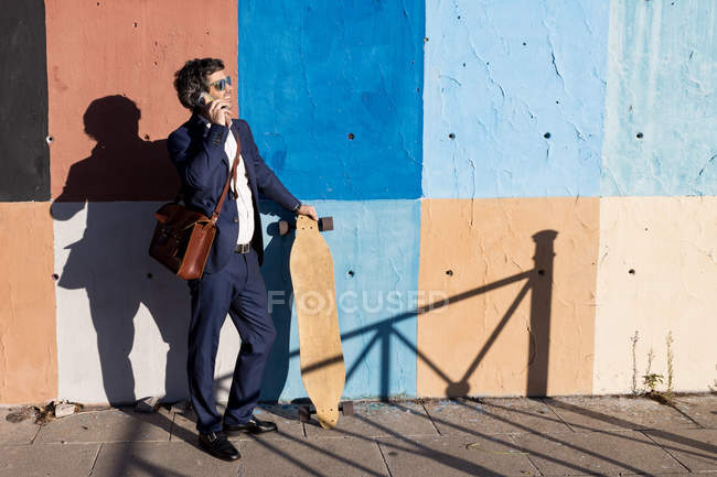 Serious businessman in elegant suit and sunglasses surfing smartphone leaning on painted wall with longboard — Stockfoto