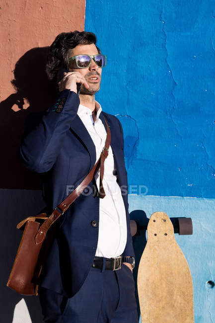 Serious businessman in elegant suit and sunglasses talking on phone leaning on painted wall with longboard — Stock Photo
