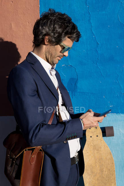 Serious businessman in elegant suit and sunglasses surfing smartphone leaning on painted wall with longboard — Stock Photo
