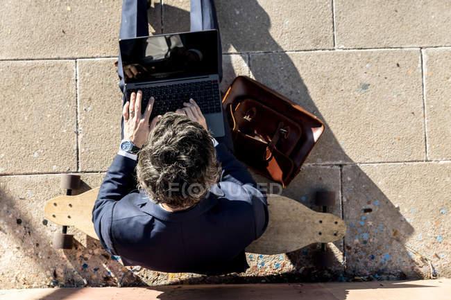 De cima de empresário anônimo em terno elegante usando laptop em escadas — Fotografia de Stock