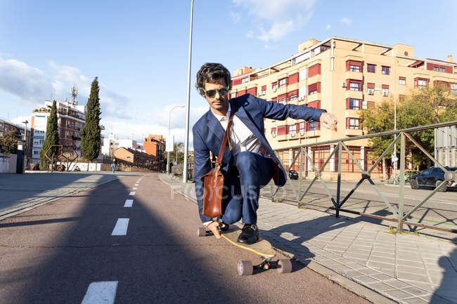 Content stylish businessman in classy suit squatting on longboard driving down paved roadway — Photo de stock
