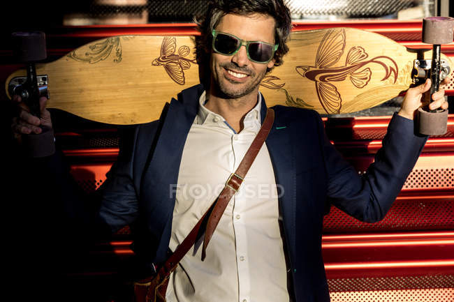Confident businessman holding wooden longboard while standing on street against red wall — Stock Photo