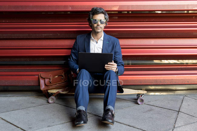 Smart businessman in elegant suit using laptop and smartphone as sitting on longboard leaning on metal red wall — Stockfoto