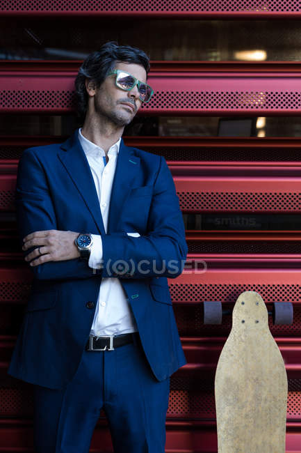 Cheerful stylish businessman in elegant suit leaning on red wall with longboard — Stockfoto