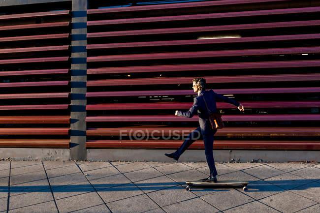 Seitenansicht eines stylischen Geschäftsmannes im Anzug, der Longboard auf der Straße entlang der metallroten Wandkonstruktion reitet — Stockfoto