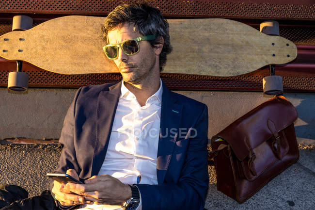 Thoughtful relaxed businessman in suit and sunglasses looking away on wooden longboard in sunny daytime — Stock Photo