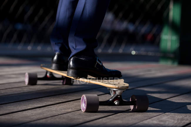 Cropped anonymous male in stylish black shoes standing on longboard on wooden road — Stock Photo
