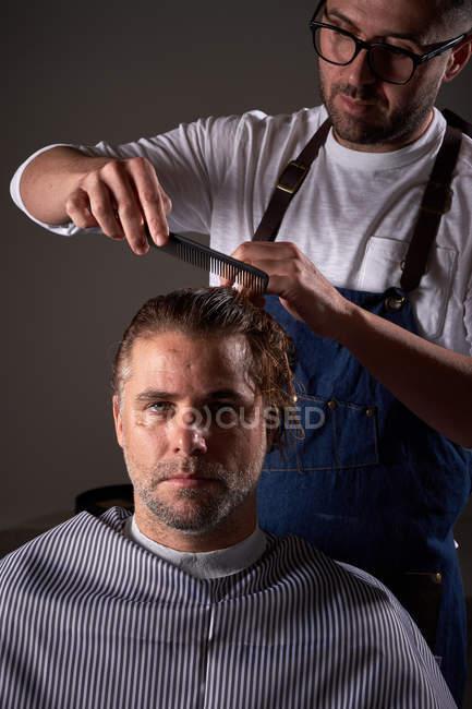 Взрослый парикмахер в белой рубашке и синем фартуке, сосредоточенный и расчесывающий длинные мокрые волосы, делая модную стрижку — стоковое фото