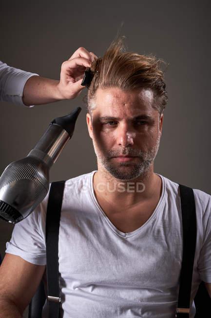 Ernte Friseur macht trendige Frisur für ruhigen brutalen selbstbewussten Mann mit Kamm und Fön vor grauem Hintergrund im Salon — Stockfoto