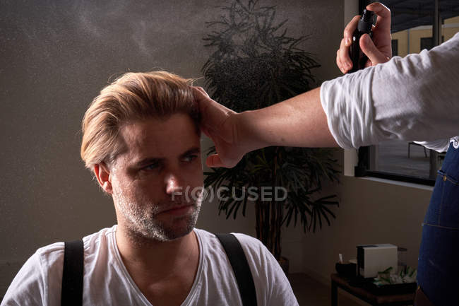 Barber touching hair and applying fixative spray while making hairstyle for man with closed eyes in cozy beauty salon — Stock Photo