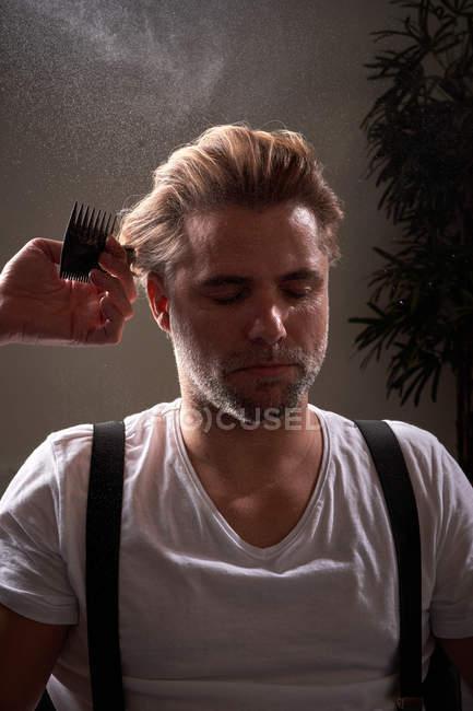 Friseur berührt Haare und wendet Fixierspray an, während er trendige Frisur für selbstbewusste, entspannte Männer mit geschlossenen Augen herstellt — Stockfoto