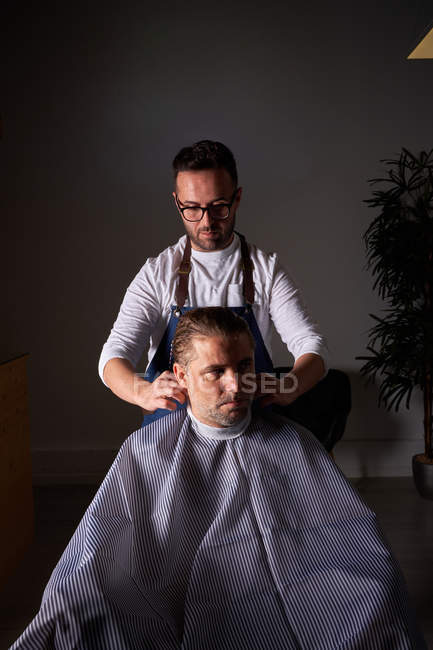 Взрослый парикмахер в белой рубашке и синем фартуке, фокусирующийся и расчесывающий длинные влажные волосы мужчины, делая модную стрижку — стоковое фото