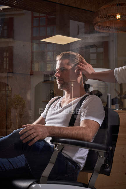 Barber touching hair and applying fixative spray while making trendy hairstyle for confident relaxed man with closed eyes — Stock Photo