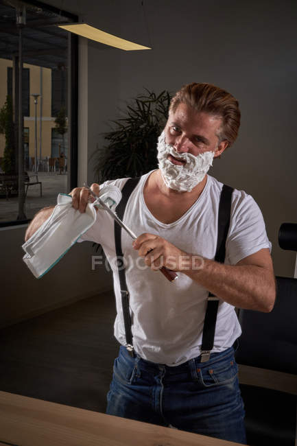 Confident brutal male in white shirt and denim pants with suspenders focusing and using big sharp knife while shaving face — Stock Photo