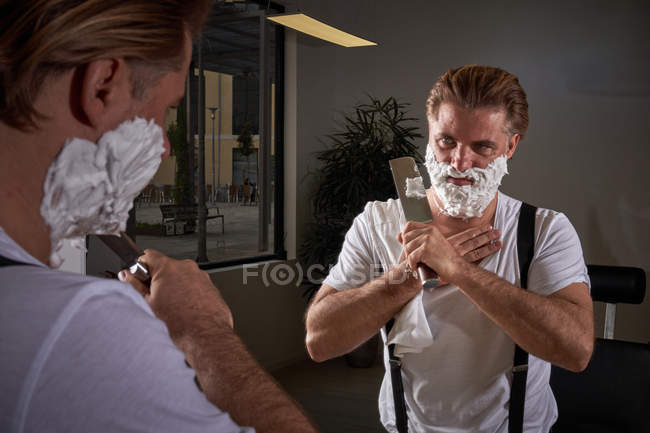 Уверенный в себе жестокий мужчина в белой рубашке и джинсовых брюках с подтяжками фокусируясь и используя большой острый нож во время бритья лица — стоковое фото