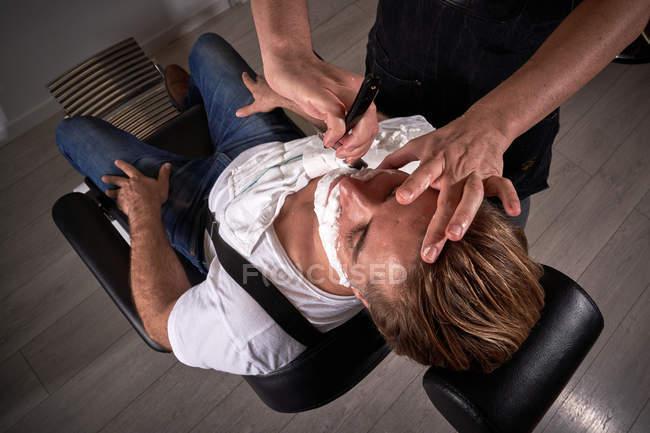 Von oben sorgfältige Ernte Friseur mit alten klassischen Rasiermesser beim Rasieren ruhig entspannter Mann mit geschlossenen Augen — Stockfoto