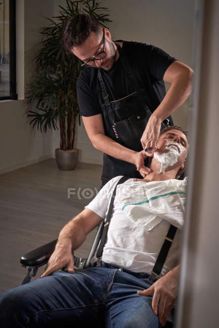 Sorgfältige Friseur mit alten klassischen Rasiermesser beim Rasieren ruhig entspannter Mann mit geschlossenen Augen sitzt im Sessel — Stockfoto