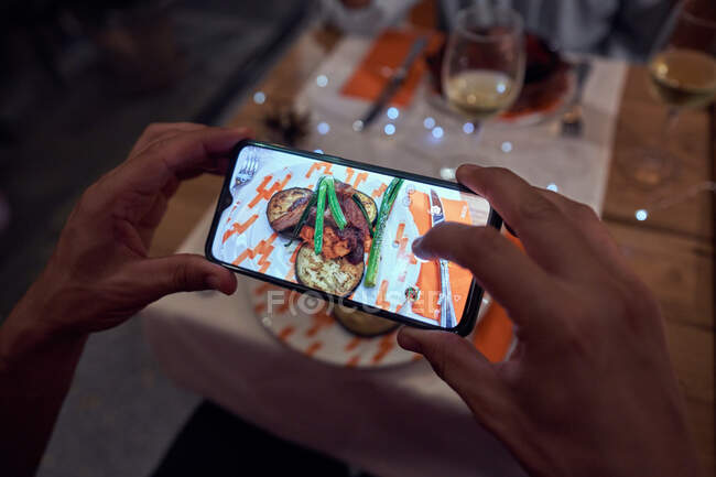 From above of crop hands of faceless man making photo of tasty dish on mobile phone while sitting at festive table at restaurant — стоковое фото