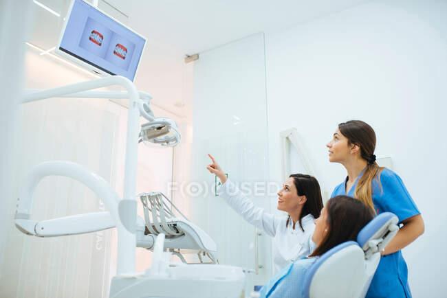 Dentista e assistente mostrando estrutura dos dentes na foto para o cliente na cadeira — Fotografia de Stock