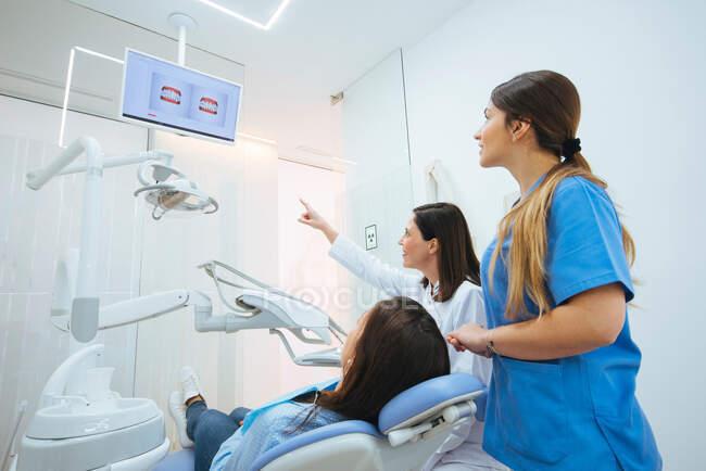 Dentista e assistente mostrando estrutura dos dentes na foto para c — Fotografia de Stock