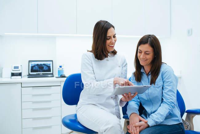 Dentista falando com o cliente mostrando documento com informações — Fotografia de Stock