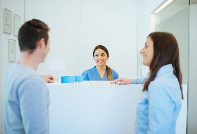Administrador alegre cumprimentando clientes na recepção da clínica odontológica — Fotografia de Stock