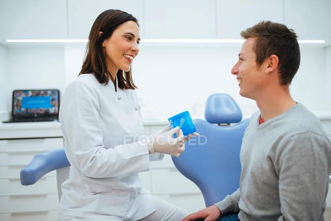 Dentista sorrindo e falando com o cliente mostrando material na caixa azul — Fotografia de Stock